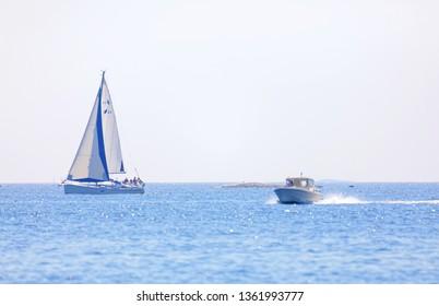 GRISSLEHAMN, SWEDEN - JUL 18, 2018: One sailship and one motor boat on the blue ocean in the swedish archipelago, islets in the background. July 18 2018, Grisslehamn, Sweden
