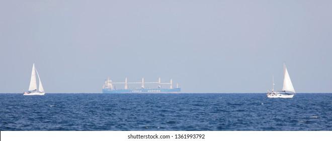 GRISSLEHAMN, SWEDEN - JUL 20, 2018: Large transport ship and two sailships on the blue ocean in the swedish archipelago. July 202018, Grisslehamn, Sweden