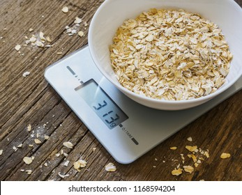 Grits in a white bowl on the kitchen scales on wooden background. Product weighing