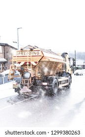 A gritting lorry travelling through heavy snow gritting the dangerous icy and snow covered roads. Black ice, bad road conditions (Shot with a slight motion blur)