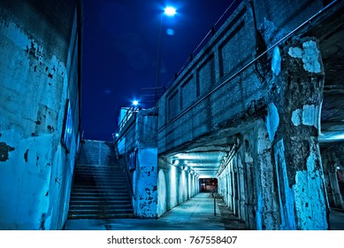Gritty dark Chicago city street under industrial bridge viaduct tunnel with a stairway to Metra train station at night.