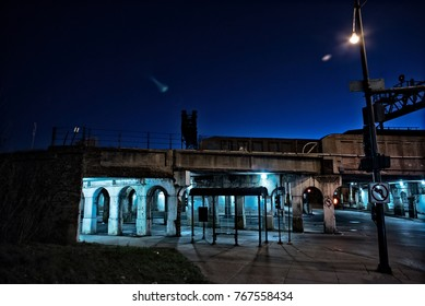 Gritty dark Chicago city street intersection under industrial train bridge viaduct tunnel with a CTA bus station at night.