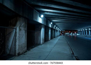 Gritty dark Chicago city street with industrial train bridge viaduct tunnel at night.