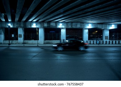 Gritty dark Chicago highway bridge and city street with a passing black car and bicycle stand at night.
