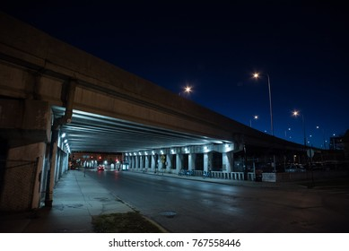 Gritty dark Chicago highway bridge and city street with a car and bicycle stand at night.