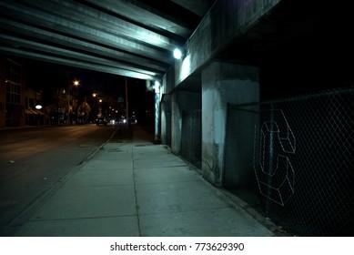 Gritty dark Chicago highway bridge underpass with traffic at night.