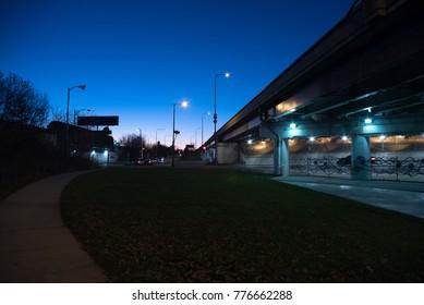 Gritty dark Chicago highway bridge underpass with traffic during twilight.