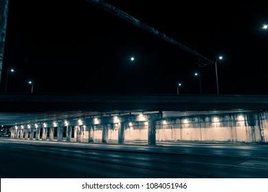 Gritty dark city highway bridge and street underpass at night