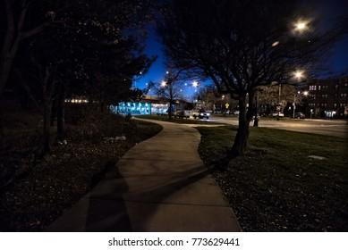 Gritty dark night scene with siedwalk, highway bridge and traffic in Chicago.
