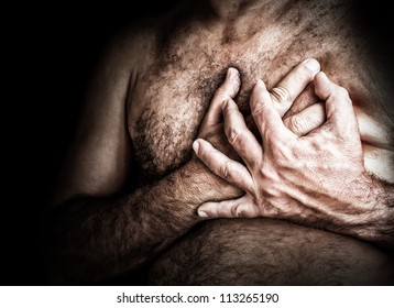 Gritty image of a shirtless man suffering from chest pain and grabbing his chest