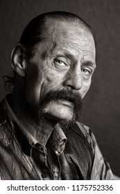 A gritty looking man with a horseshoe mustache and black, leather jacket.  He has his mouth partially open in a conversation with the photographer.  Gritty black and white.