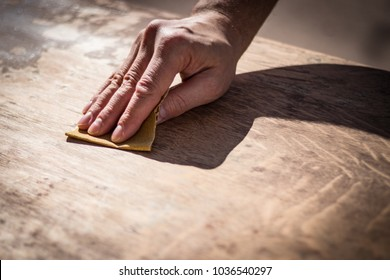 Gritty weathered man's hand and sandpaper; hand sanding a table top to refinish with paint or stain