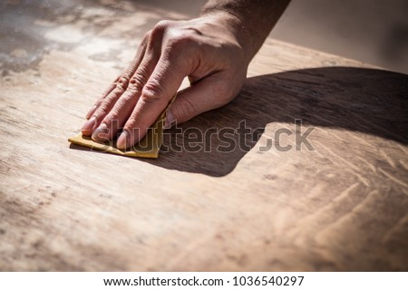 3b20ae14d Gritty weathered man s hand and sandpaper  hand sanding a table top to  refinish with paint