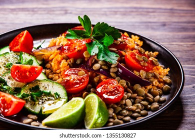 Groats with lentils and vegetables on wooden table