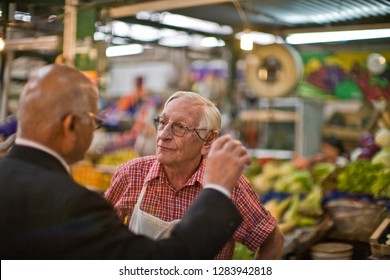 Grocer and his customer talking at a market.