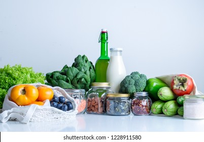 groceries in eco cotton bags, glass gars and botles on white table