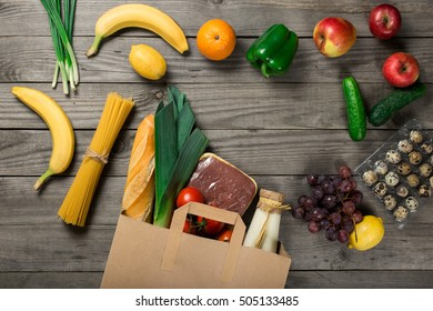 Groceries in paper bag on wooden table, top view