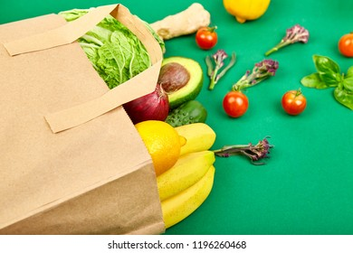 Grocering concept. Full paper bag of different fruits and vegetables,  ingredients for healthy cooking on a color background. healthy food.  Diet or vegan food, vegetarian. Top view. Flat lay.