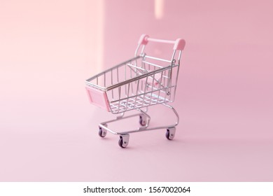 Grocery cart on pink background, shopping in supermarket