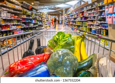 Grocery cart in supermarket filled with food products seen from the customers point of view