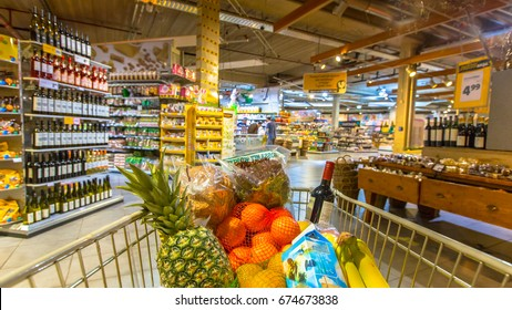 Grocery cart at a supermarket filled up with food products as seen from the customers point of view