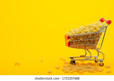 A grocery cart to the top is filled with pasta on a bright orange background, some pasta is lying next to the cart