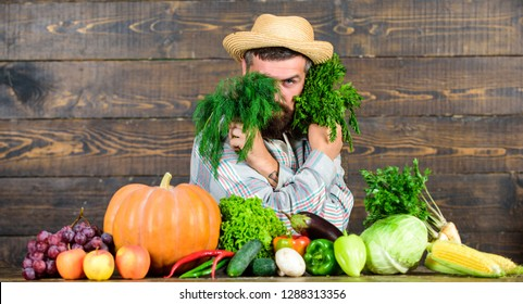 Grocery shop concept. Buy fresh homegrown vegetables. Excellent quality vegetables. Man with beard proud of his harvest vegetables wooden background. Farmer with organic vegetables. Just from garden.