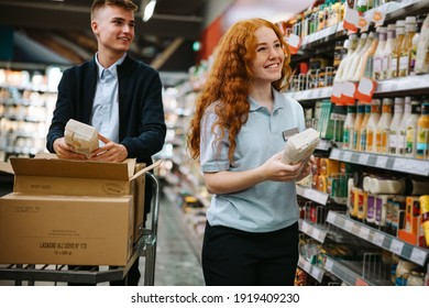Grocery shop workers working in the store. Two new employees working together and restocking the shelves.