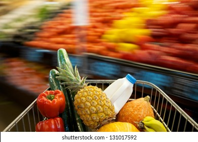 A grocery shopping cart filled with different products including milk, banana's, cucumbers and pineapple with a motion blurred background