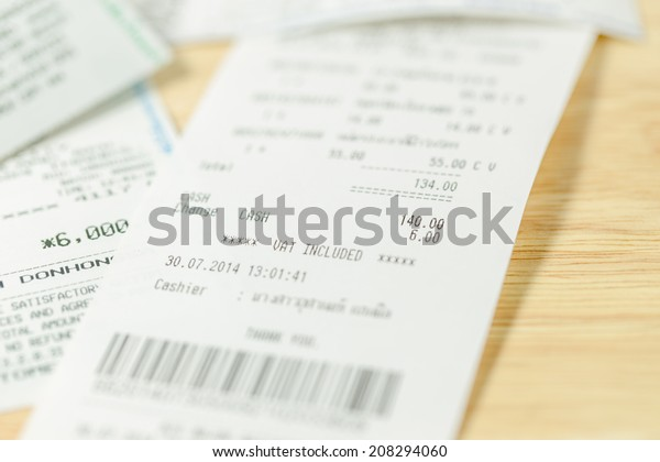 Grocery shopping list on a till roll printout on wood board background