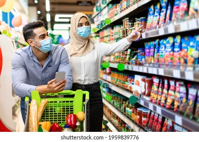 Grocery Shopping. Muslim Couple Choosing Food In Supermarket, Arabic Wife In Hijab And Protective Face Mask Pointing Finger On Shelf With Products. Islamic Family Purchasing Essentials In Store