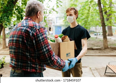 A grocery store delivery man wearing a black polo-shirt delivering food to an old man at home