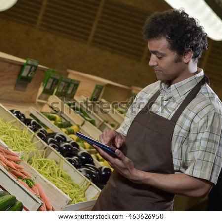 grocery store employee reading inventory list stock photo edit now