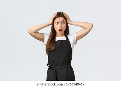 Grocery store employees, small business and coffee shops concept. Troubled alarmed barista grab head and drop jaw concerned, hear shocking news, react astonished, standing white background