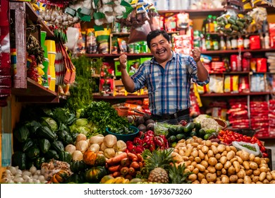 Grocery store in Guatemala with successful man celebrating, standing in a boxing position.