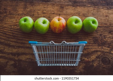 grocery store mini shopping basket with one single red apple among other green ones on wooden table, concept of picking the best produce