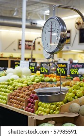 Grocery store scale with fruit and veg in background