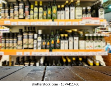 Grocery store. Shelves with olive, rapeseed and sunflower oil. Defocused, blurred image. In the foreground is the top of a wooden table, counter.