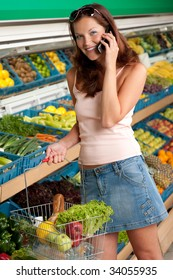 Grocery store - Smiling woman with mobile phone in a supermarket