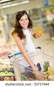 Grocery store - smiling woman shopping with trolley in supermarket, holding orange