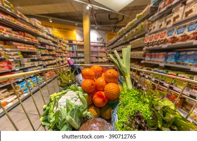 Grocery trolley cart at a supermarket aisle filled up with healthy food products seen from the customers point of view