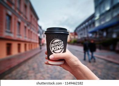 Grodno, Belarus - 13 Jul 2018. Young woman with a paper cup of coffee in hand from Burger King take away. Girl  drink coffee on the street of the city while walking in the evening.