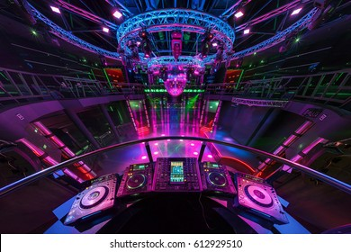 GRODNO, BELARUS - JULY 13, 2013: DJ mixing music on console at the colorful interior of european stylish night club with bright lights with disco mirror ball