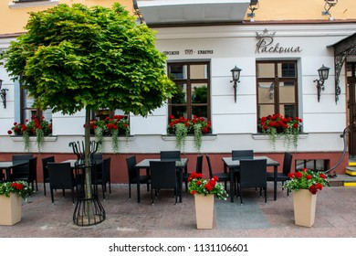"Grodno / Belarus - June 2018:  Ancient Restaurant ""Roskosha"" in the downtown. A summer terassa with red flowers in pots."