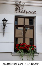 """Grodno / Belarus - June 2018:  Ancient Restaurant """"Roskosha"""" in the downtown. A summer terassa with red flowers in pots."""