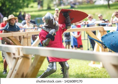 GRODNO, BELARUS - JUNE 2019: medieval jousting knight fight, in armor, helmets, chain mail with axes and swords on lists. historic reconstruction of ancient fight