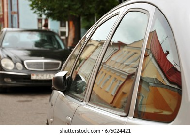 Grodno, Belarus - June 25, 2017: Mirror glass of the car reflecting the houses of the old city.