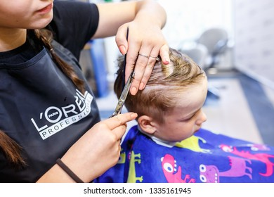 GRODNO, BELARUS -  MAY 2016: master hairdresser coiffeur doing a hairstyle in barber salon for small boy teenager