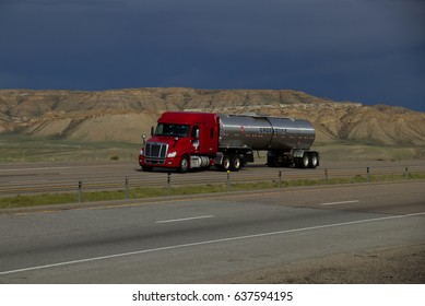 Groendyke Tanker  A red Freightliner Tractor pulls a silver tanker trailer along a Rural Wyoming interstate. May 7th, 2017 Rock Springs, Wyoming, USA