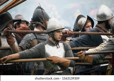 Groenlo,Gelderland/Netherlands - 10-19-2019: Reenactment historic 17th century war, young man in the middle of the siege. Intense face looking to the right. Holding spear, full armour. Spanish soldier
